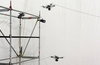 Watch as a trio of flying drones build a working rope bridge